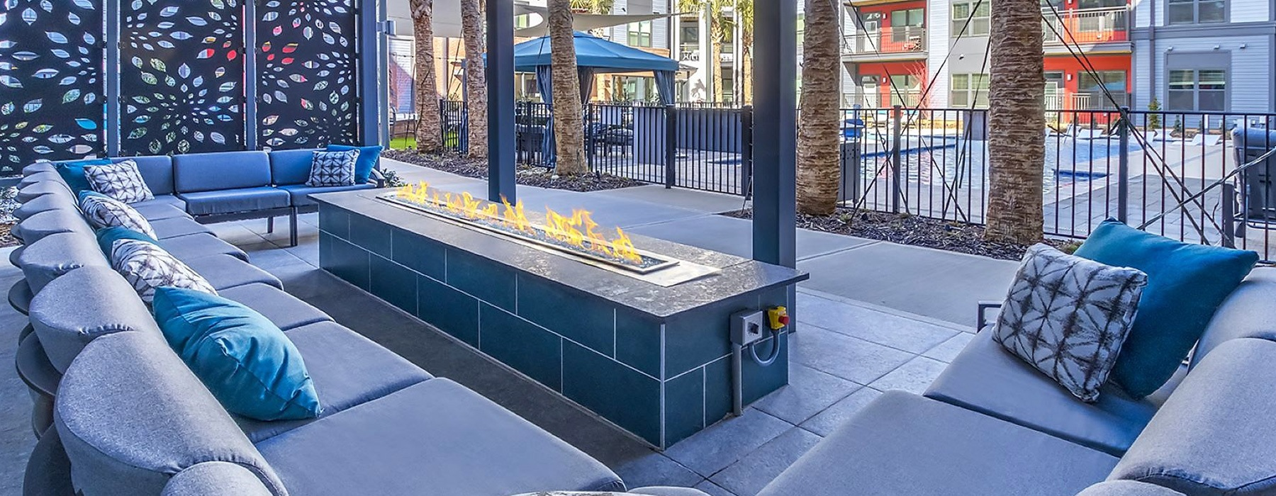spacious seating around a fire pit beside the pool area