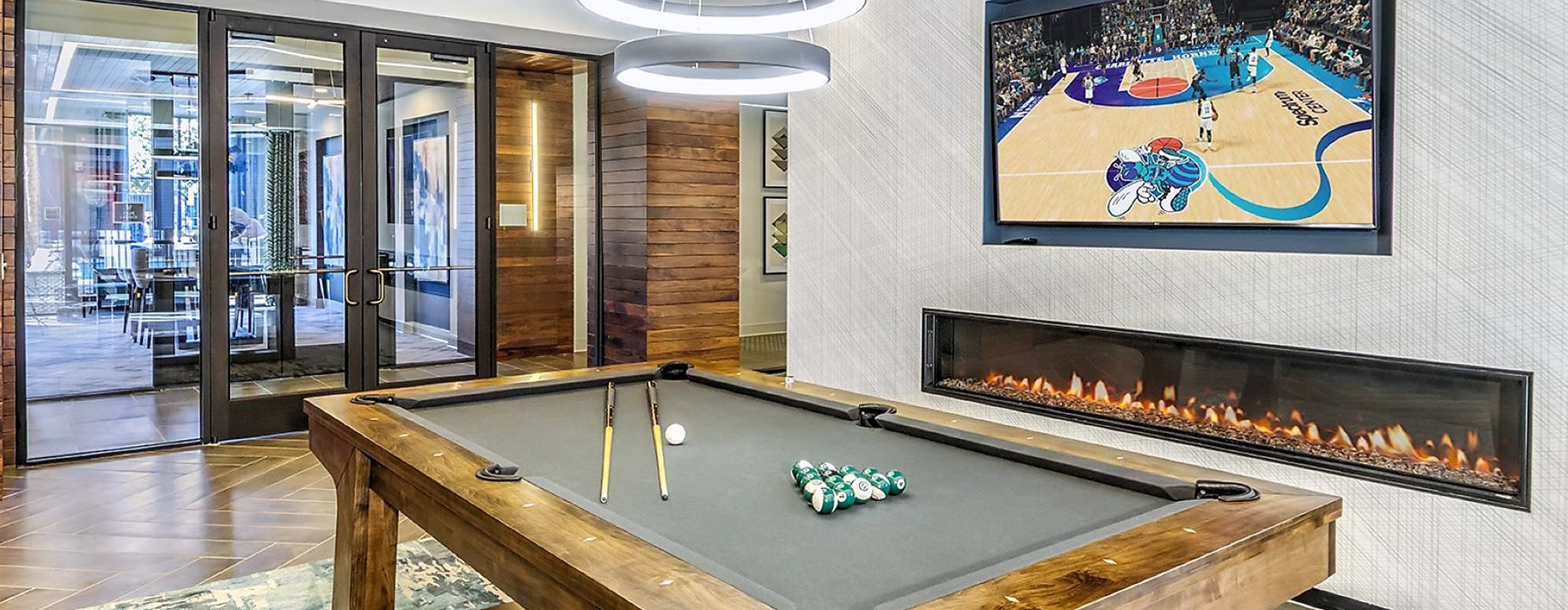 pool table in spacious game room with modern decor such as built-in fireplace in near wall