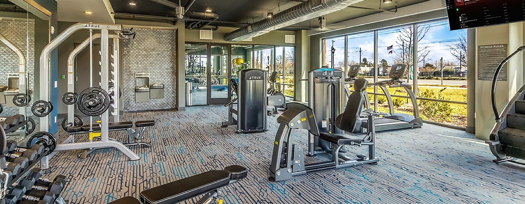 spacious fitness center with equipment and gorgeous views of area through wall-to-wall style windows